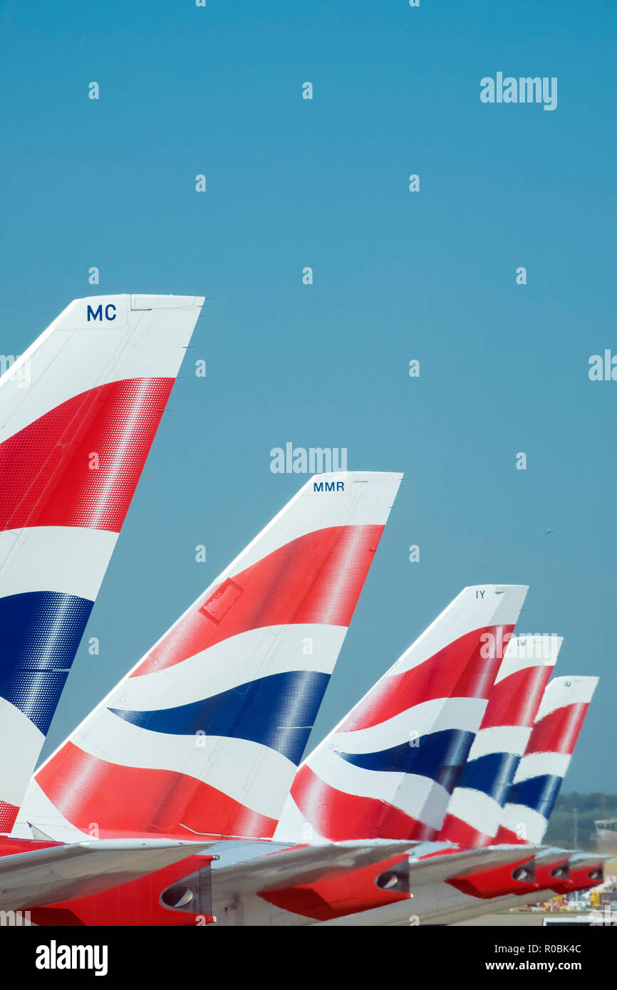 British Airways tailfins showing the company logo on aeroplanes parked in London Heathrow - Stock Image