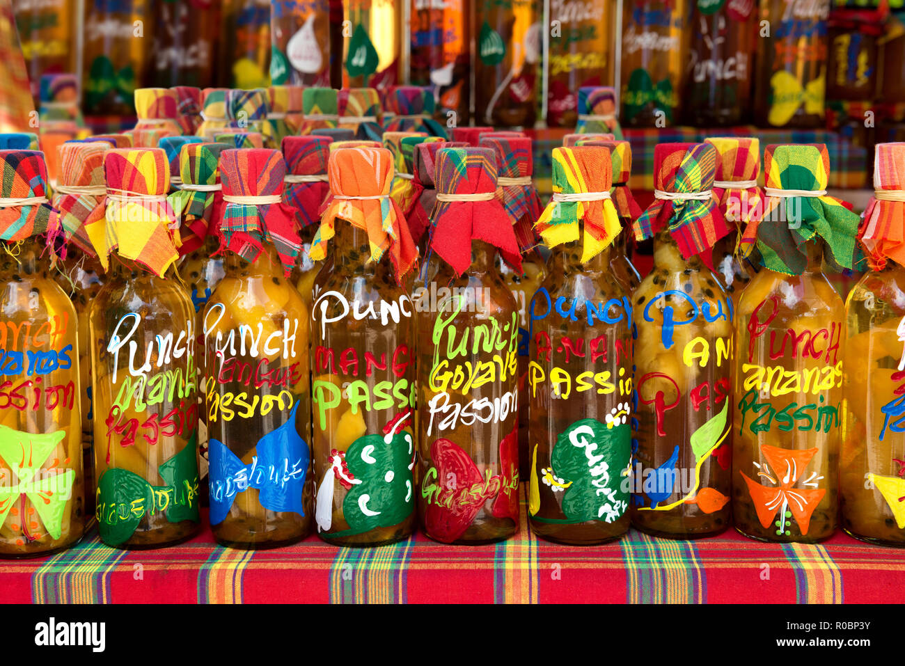 many different colored punch(rum and tropical fruits) bottles in a row on a typical market,guadeloupe, french west indies. - Stock Image