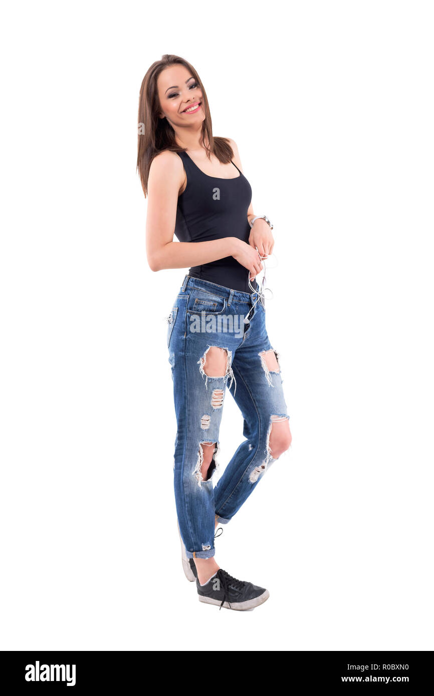 44d7f9616d652 Relaxed young stylish woman posing wearing torn jeans and black top smile.  Full body isolated on white background.
