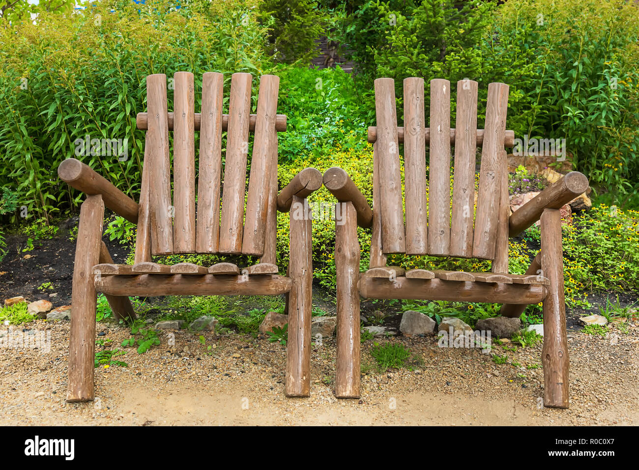 Wooden chairs made of rough wood trunks for relaxing in a park on the nature Stock Photo