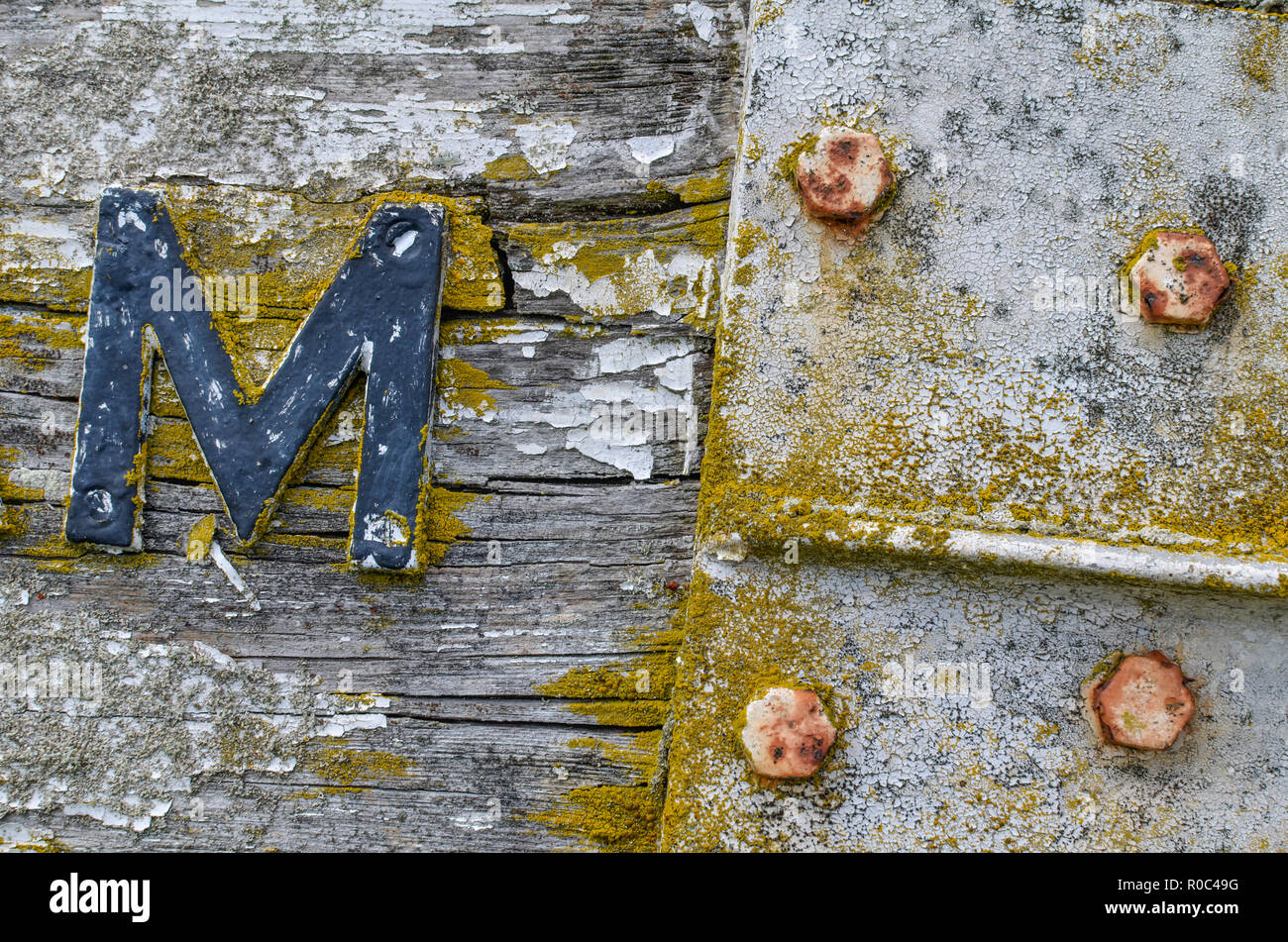 Close-up of the weathered metal and wood surfaces of a rural road sign. - Stock Image