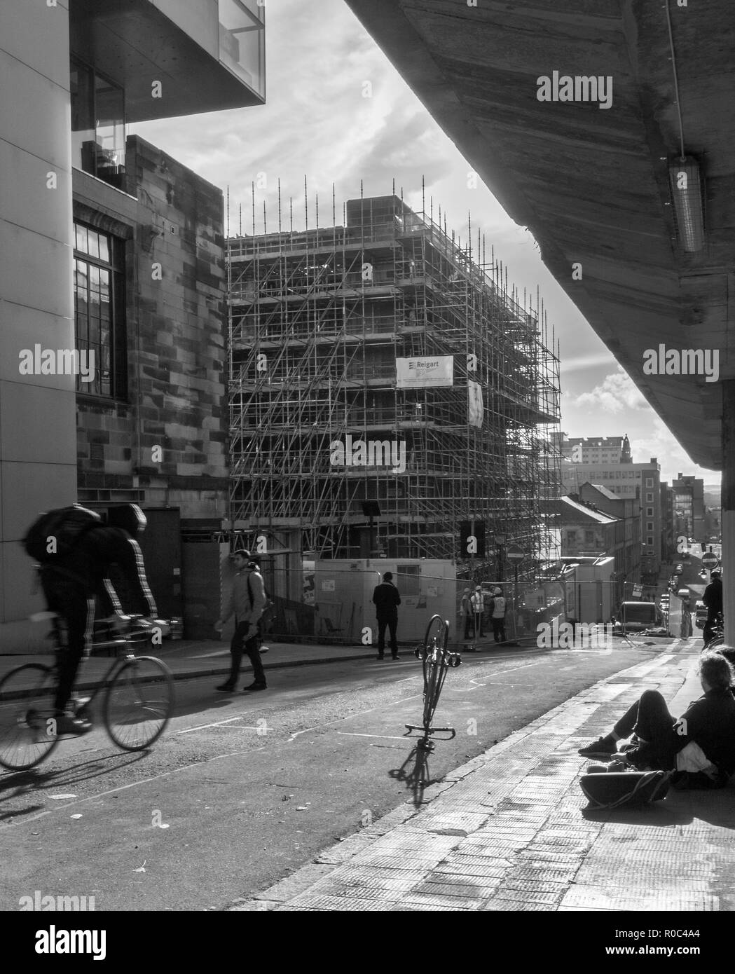 GLASGOW, SCOTLAND - NOVEMBER 2nd 2018: A black and white photograph of a students going to class while workers work on the site of Glasgow School of A - Stock Image