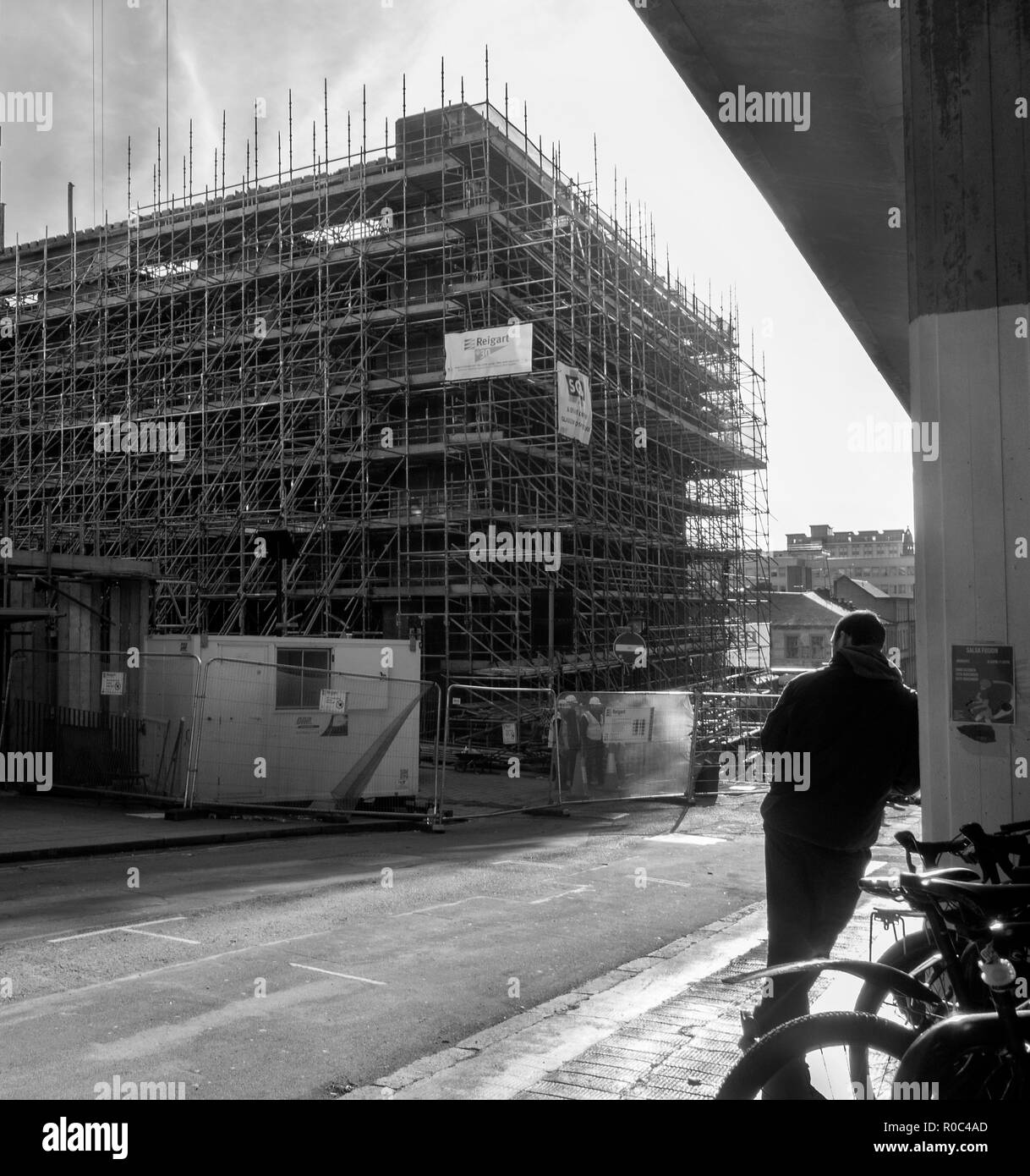 GLASGOW, SCOTLAND - NOVEMBER 2nd 2018: A black and white photograph of a man leaning on a wall while workers work on the site of Glasgow School of Art - Stock Image