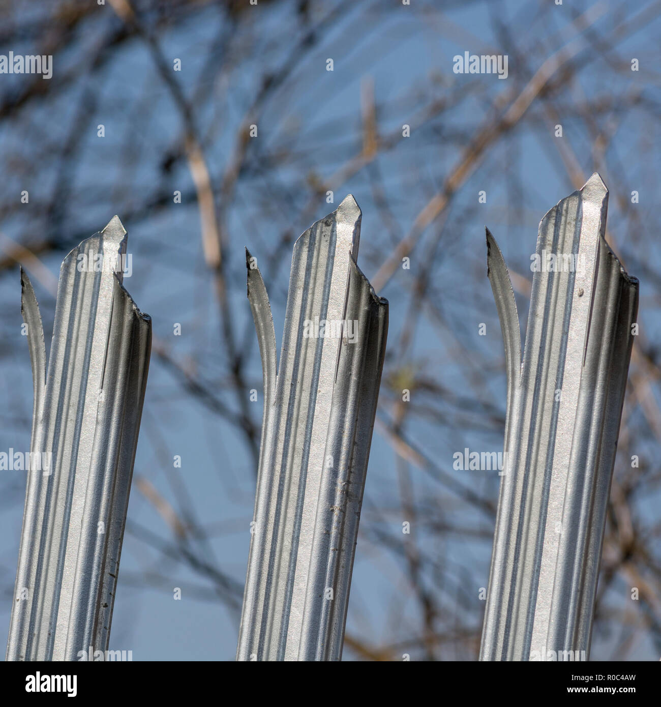 Robust galvanised anti-climb steel fence - metaphor 'Keep Out', concept of barriers and US Mexico border wall, barriers to change, protection security - Stock Image