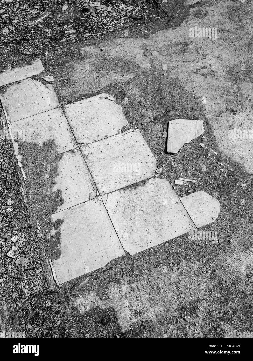 Old kitchen floor tiles in a demolished house. B&W version of R0C4C1. - Stock Image