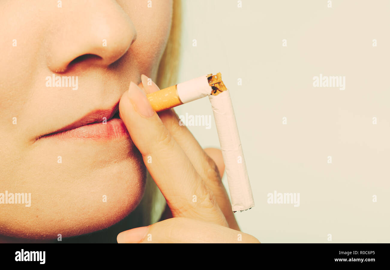 Smilling pretty girl smoking breaked down cigarette. Winning with addicted nicotine problems in young age. Quitting from addiction concept. - Stock Image