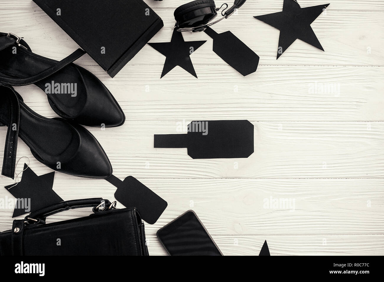 Black bag, gift box, black price tags, phone, shoes on white background flat lay. Space for text. Christmas shopping and sales. Stylish Black Friday.  - Stock Image