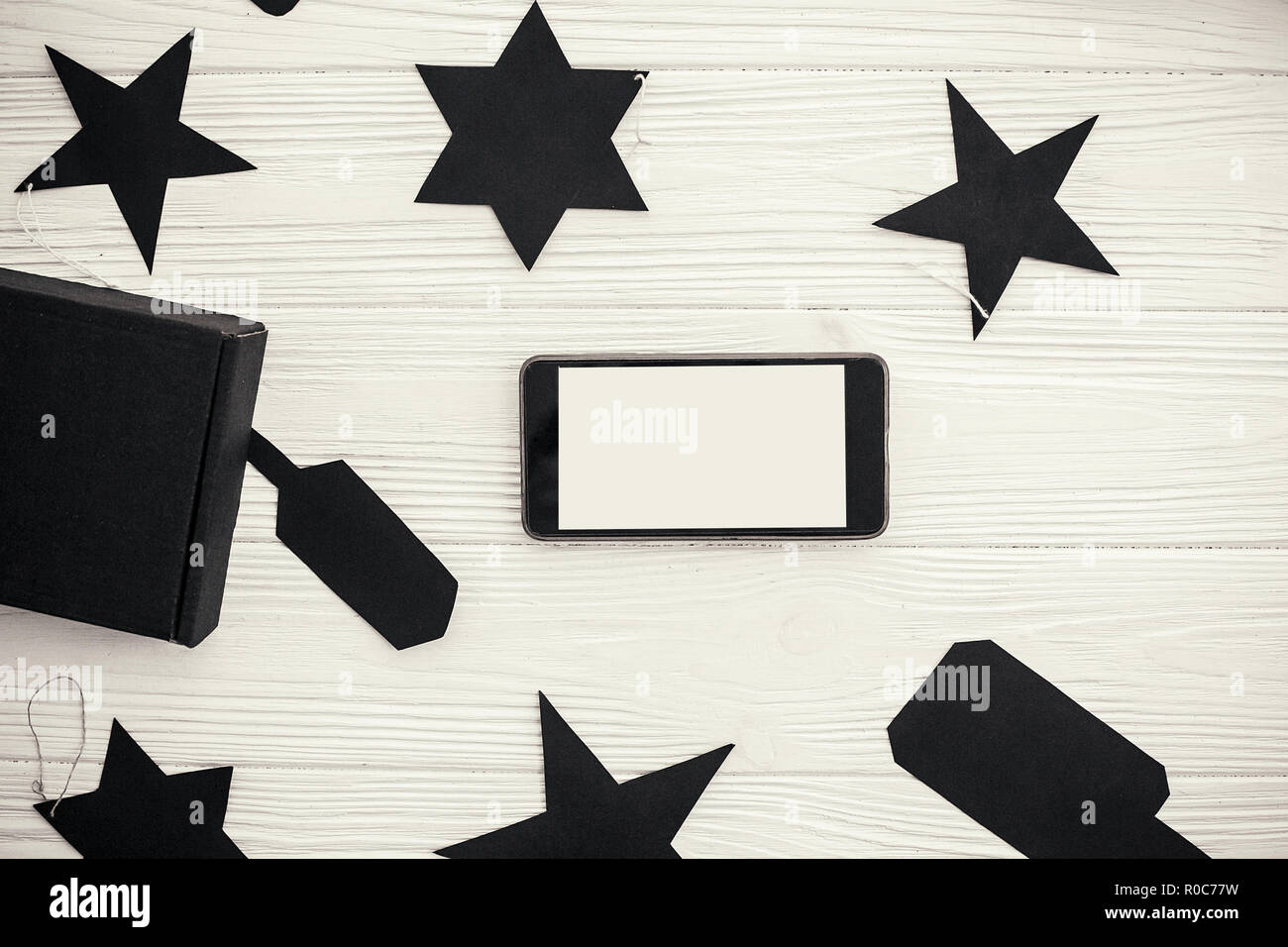 Black Friday Sale flat lay. Phone with empty screen black gift box and price tags on white background. Space for text. Christmas shopping and sales. A - Stock Image