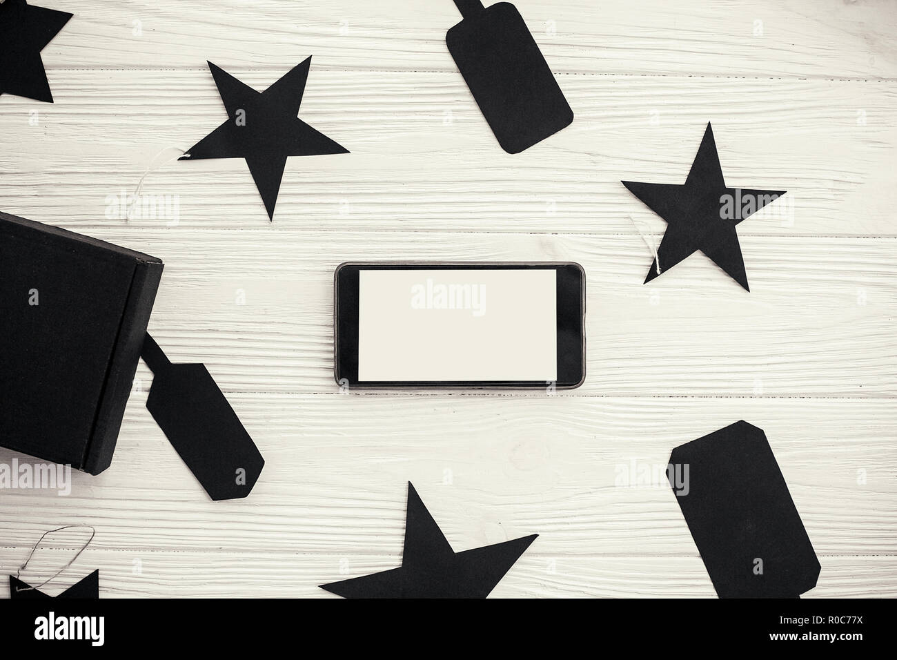 Phone with empty screen black gift box and price tags on white background. Space for text. Black Friday Sale flat lay. Christmas shopping and sales. A - Stock Image