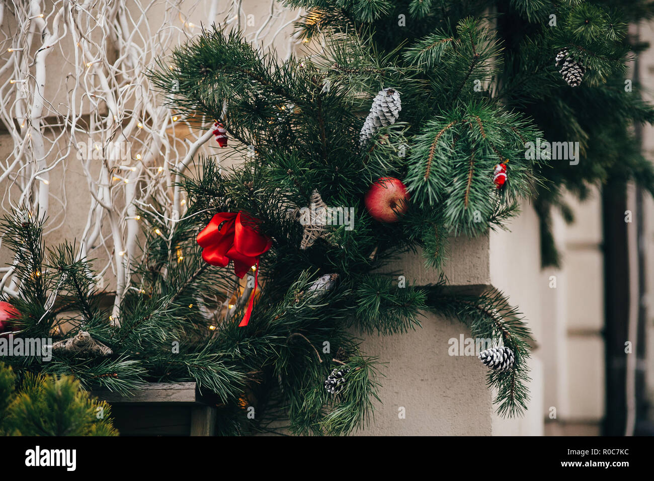 Stylish christmas decorations, green christmas wreath with red bows and ornaments, pine cones, stars, white branches in european city street. Festive  - Stock Image