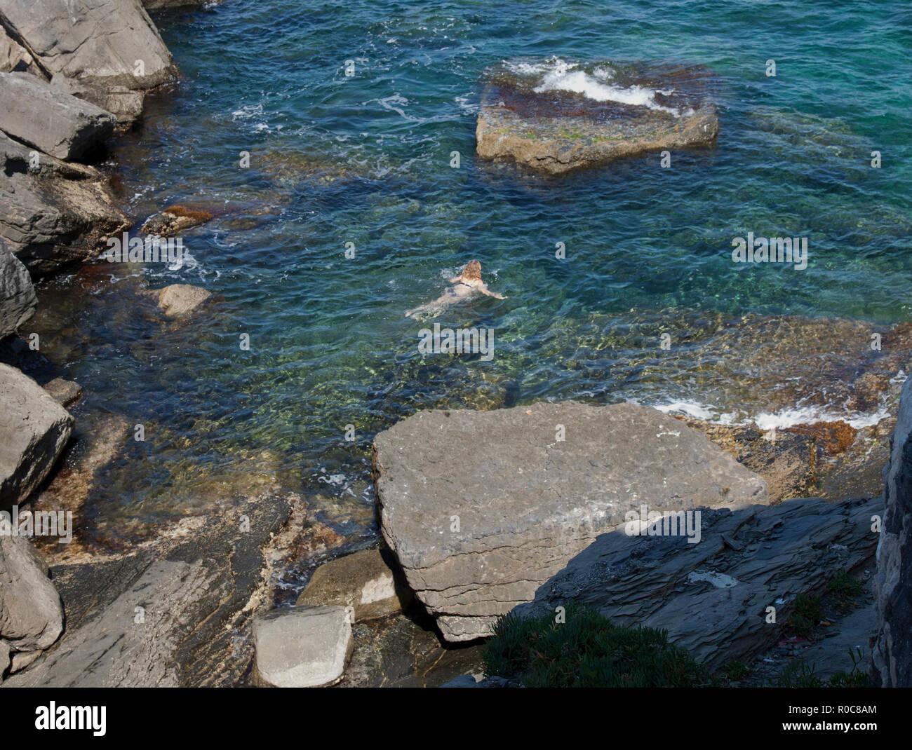 Young Girl Swimming, Bay of Poets, Rocky Coast, Portovenere, La Spezia, Italy. - Stock Image