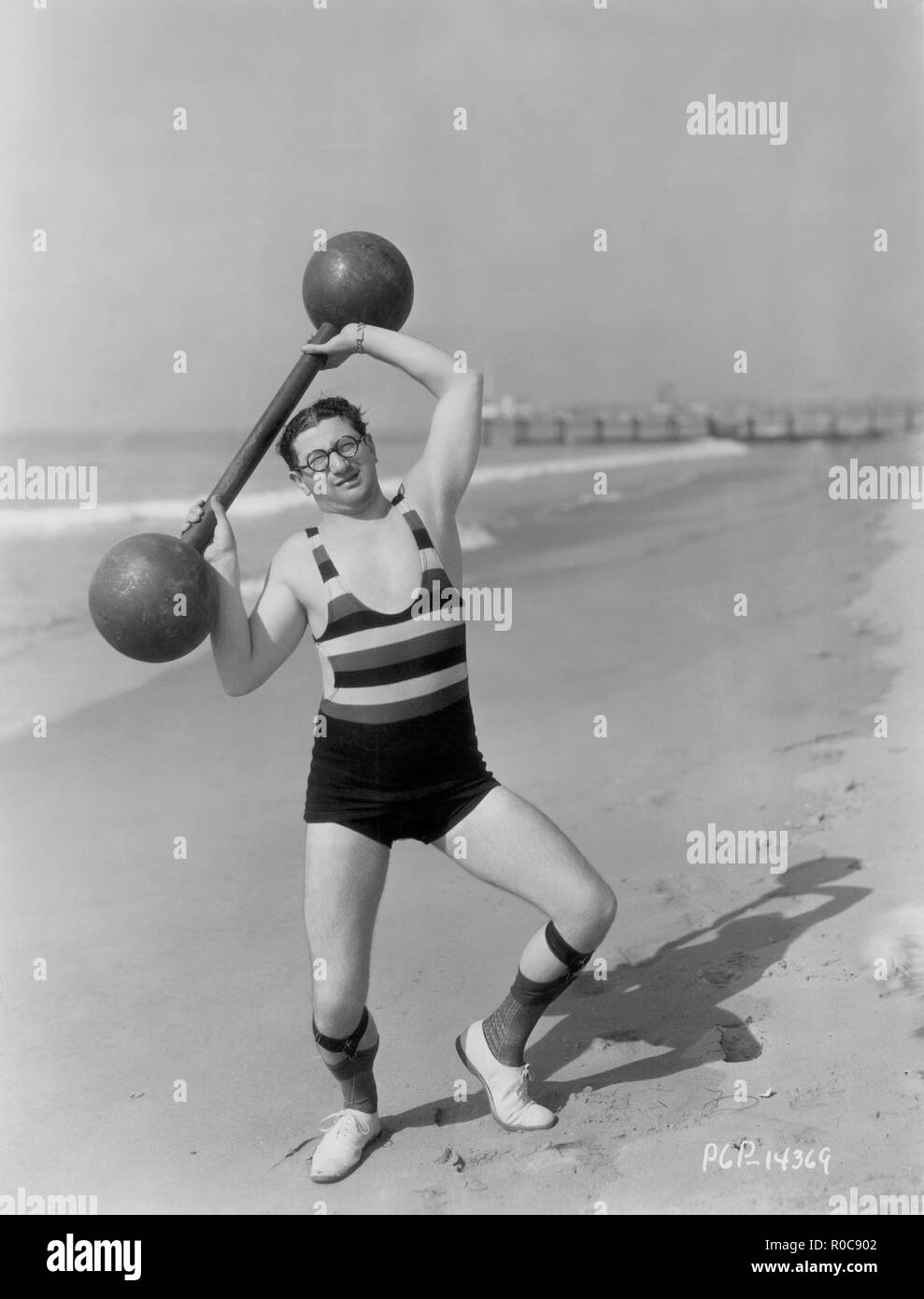 Actor Harry Green, Publicity Portrait Lifting Barbell on Beach, early 1930's - Stock Image