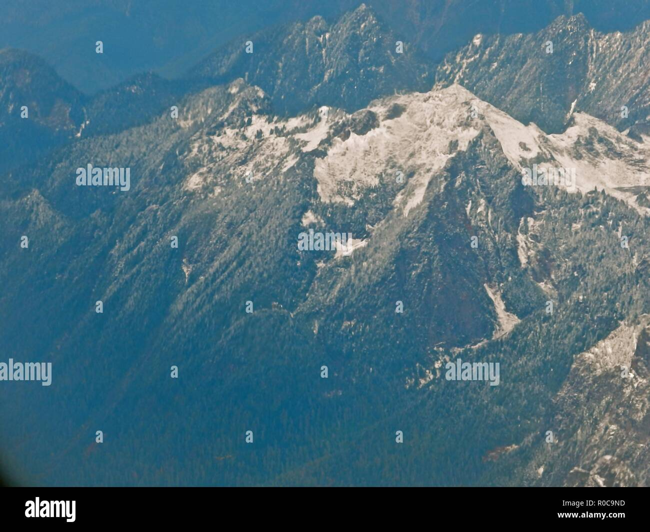 Airplane view of the North Cascade Mountain range, also known as the Pacific Ring of Fire, due to the many volcanoes located there. - Stock Image