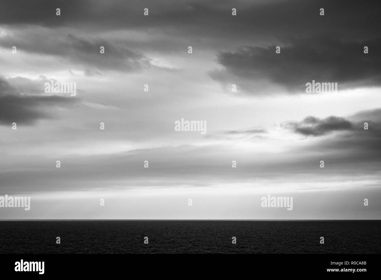 Black and white image of imposing cloudy sky over a flat ocean. View from Magdalen Islands, Quebec, Canada. - Stock Image