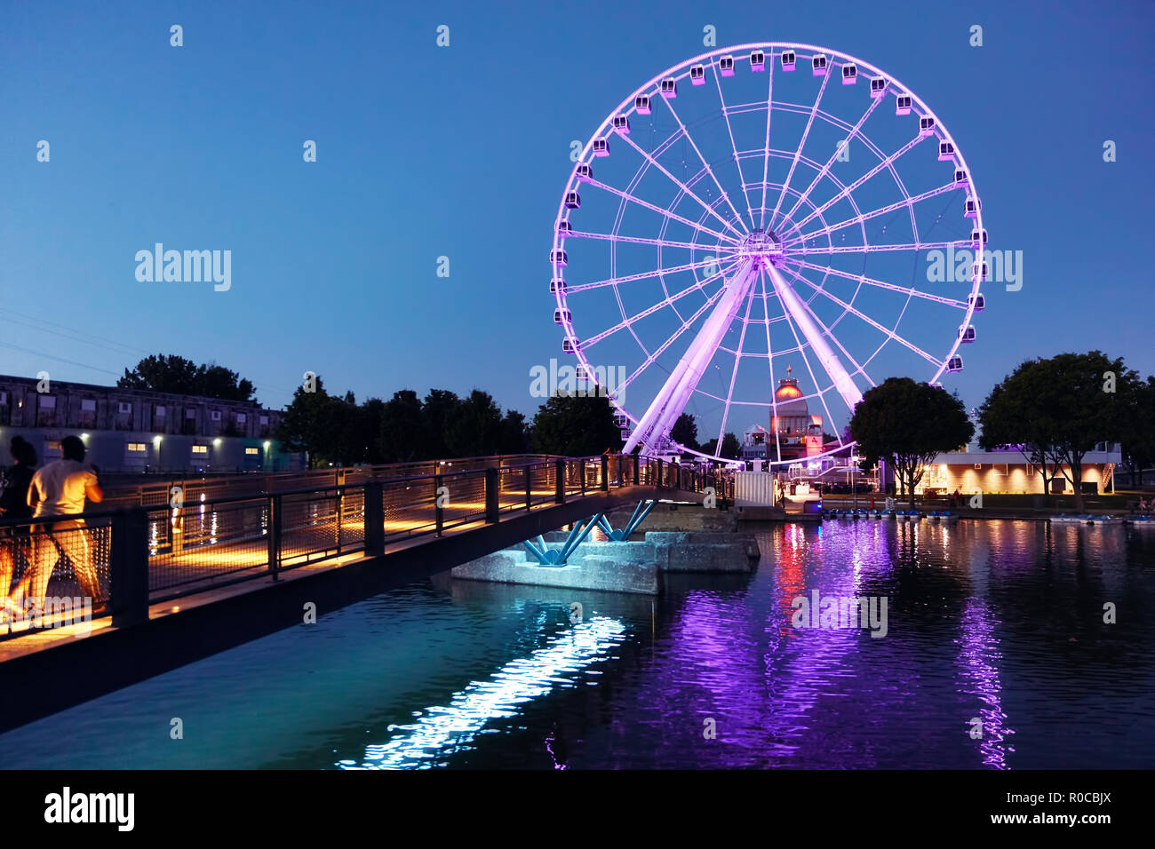 Illuminated ferris wheel (observation wheel) in old port at the blue hour of a summer evening in Montreal, Quebec, Canada - Stock Image
