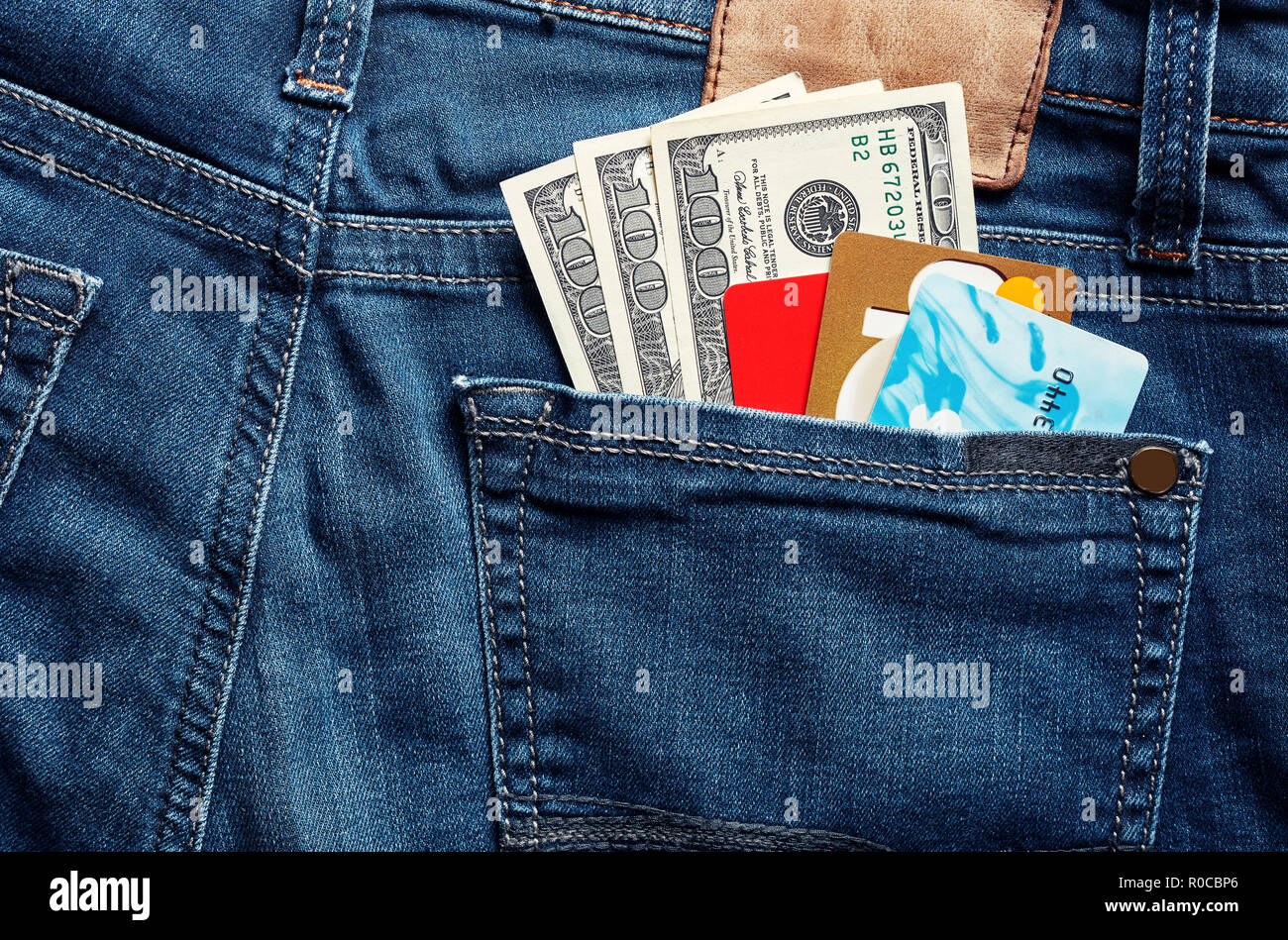 Colorful credit cards and 100 usd dollar bills in a blue jean back pocket. - Stock Image
