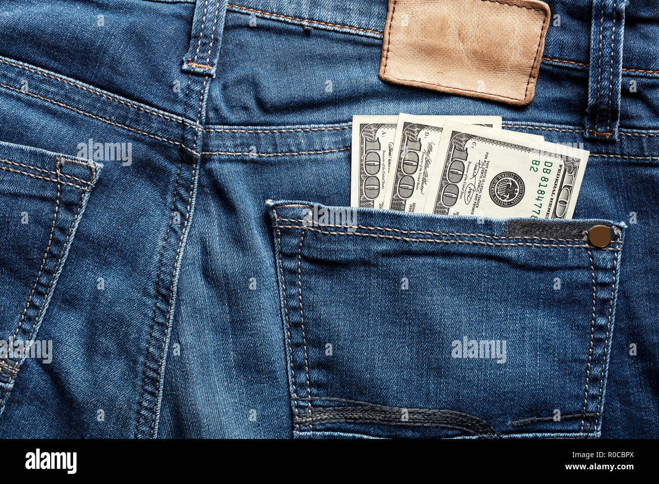 One hundred dollar bills in the back pocket of a blue jean. Working class wage. - Stock Image