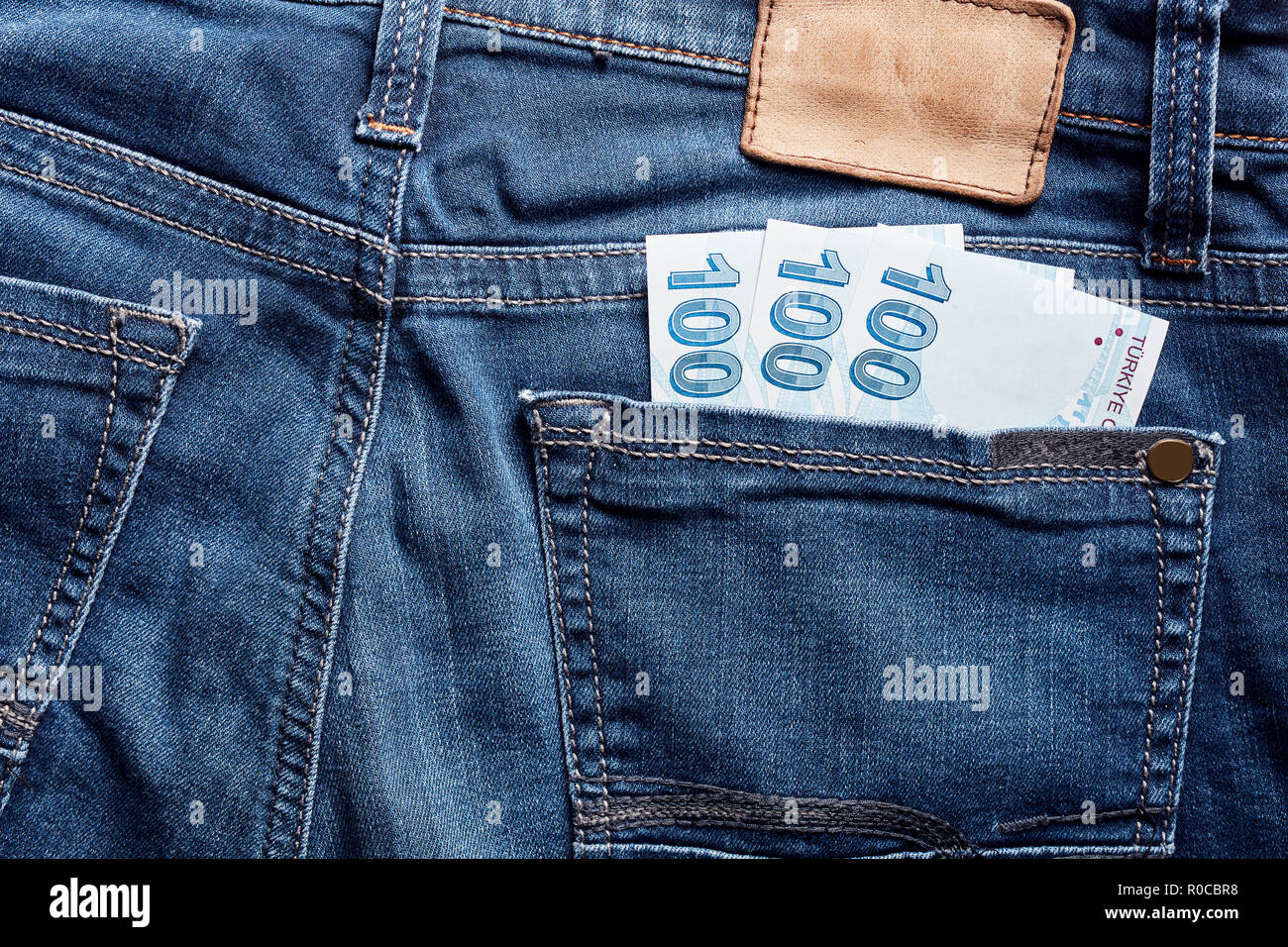 One hundred Turkish Lira bills in the back pocket of a blue jean. Stock Photo