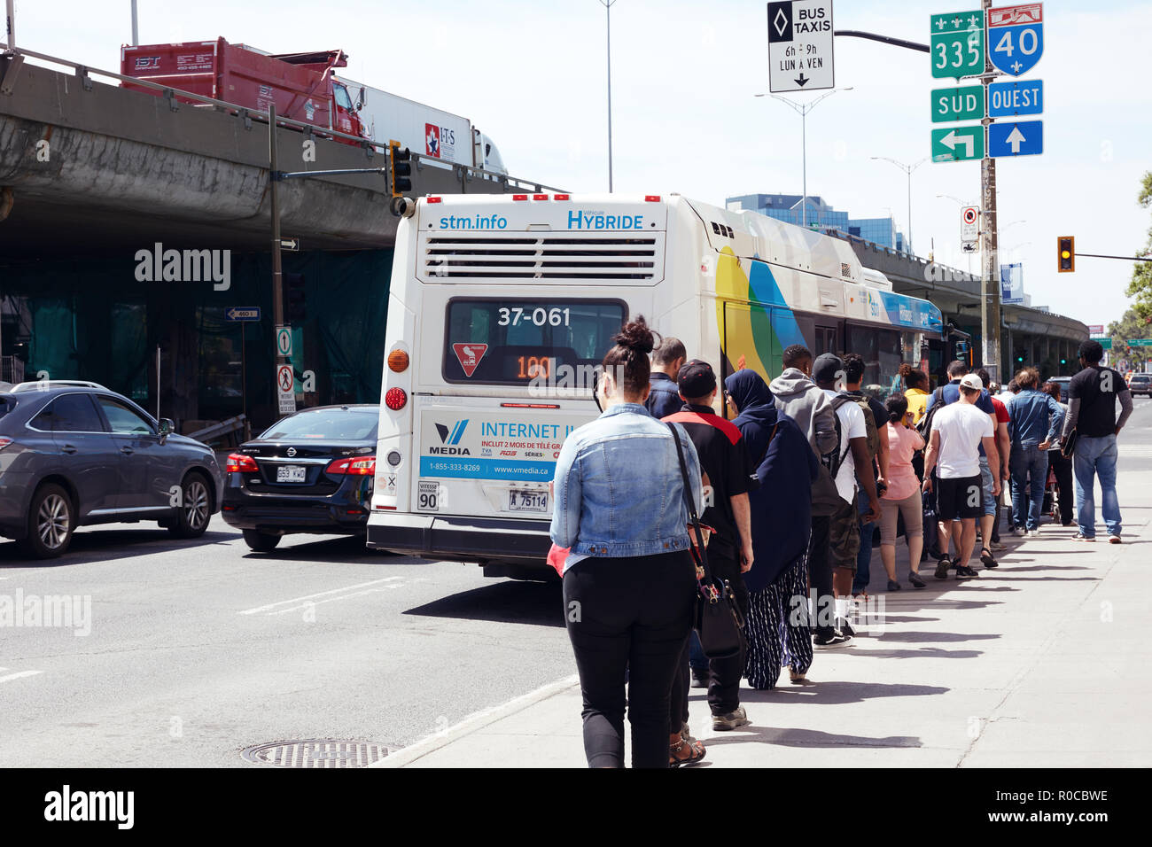 People waiting in queue on the public bus station to get on the bus in Montreal, Quebec, Canada. Stock Photo