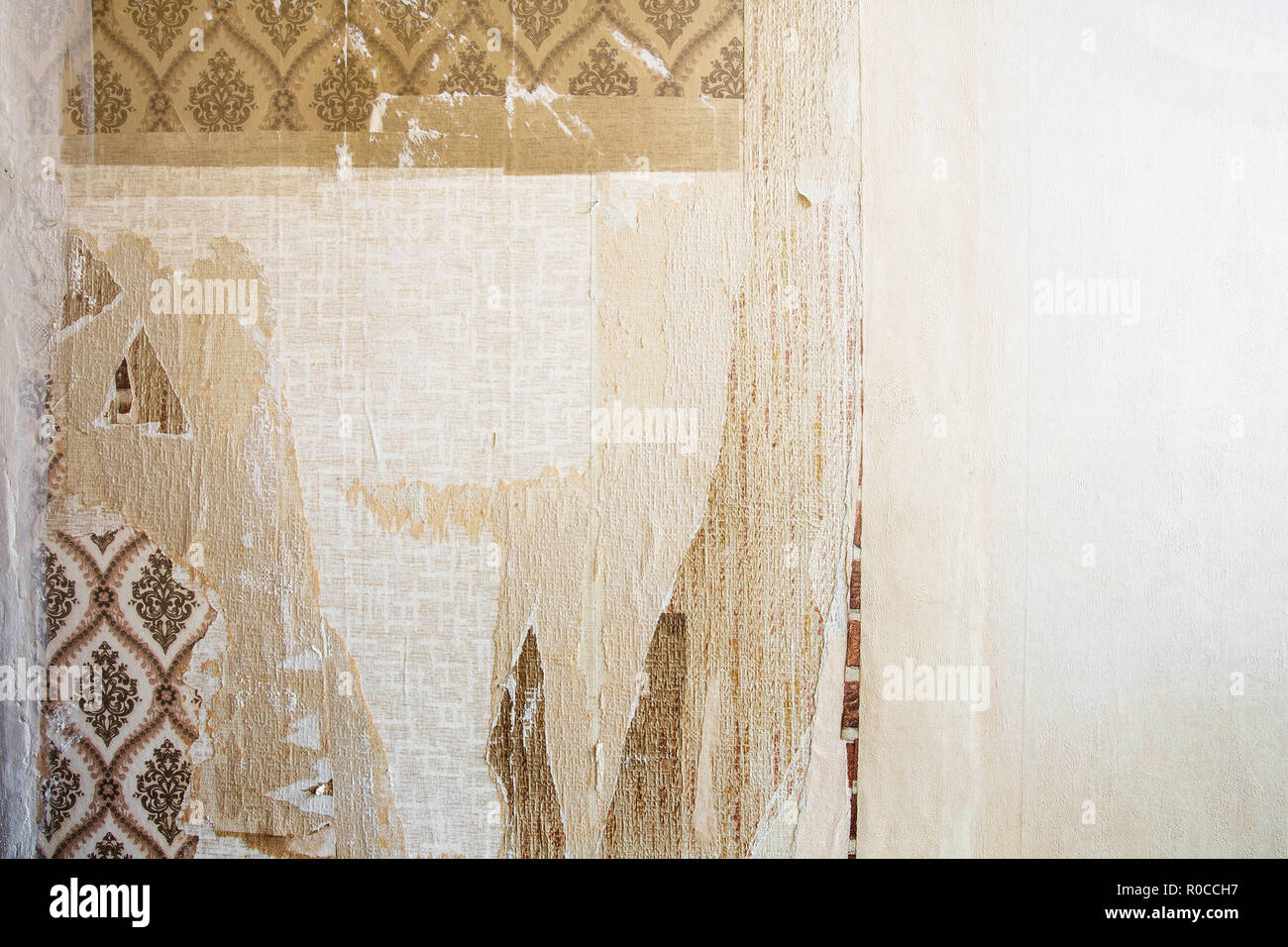 Aged room wall background with torn vintage wallpaper, old background texture - Stock Image