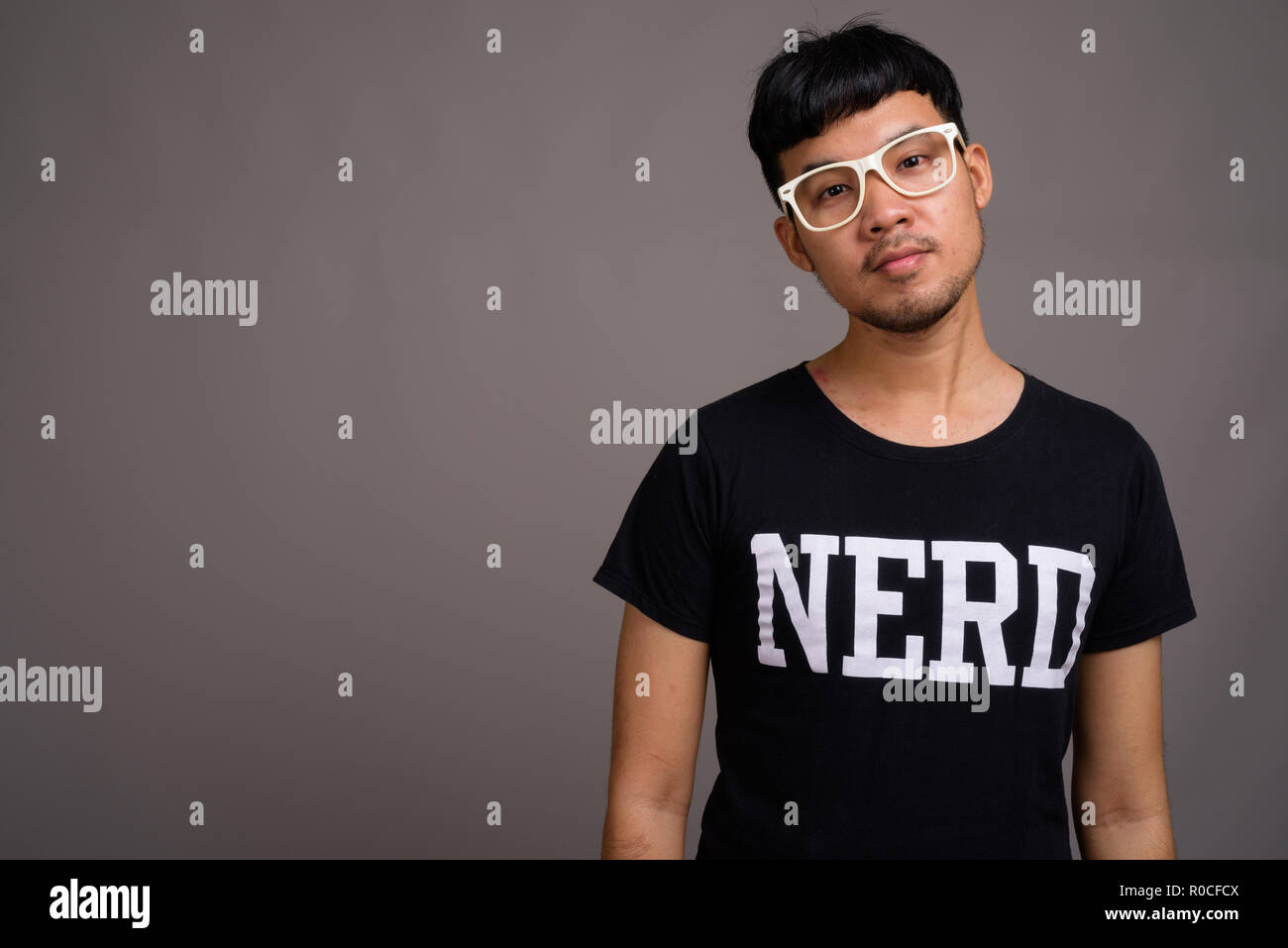 23ada37ba9fc Young Asian nerd man wearing eyeglasses against gray background - Stock  Image