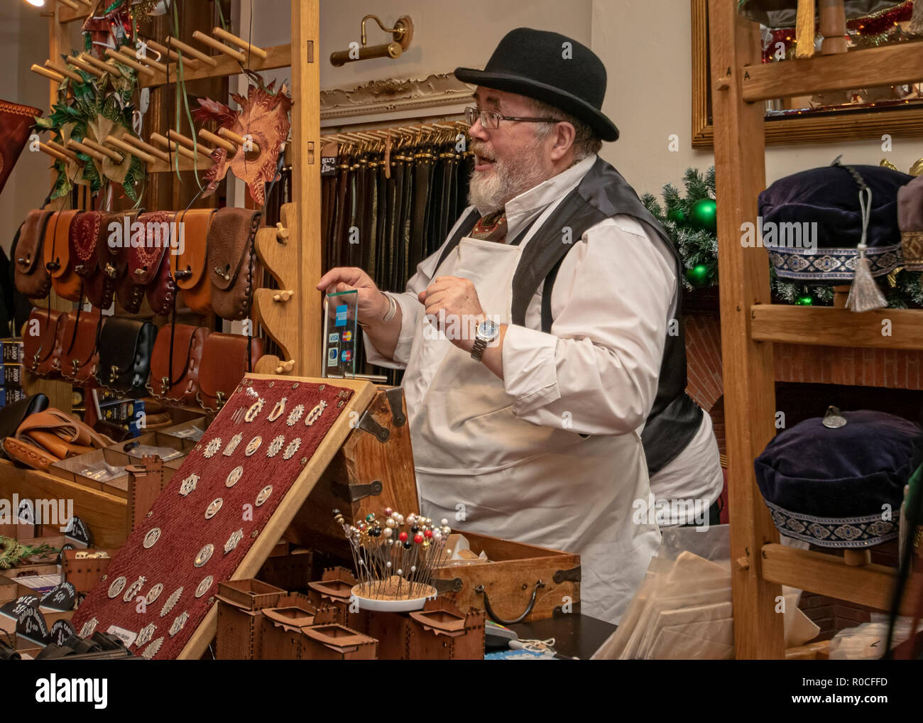 UK, Market Bosworth, Victorian Christmas Fair - December 2015: marker trading selling leather goods dressed in as a victorian shopkeeper - Stock Image