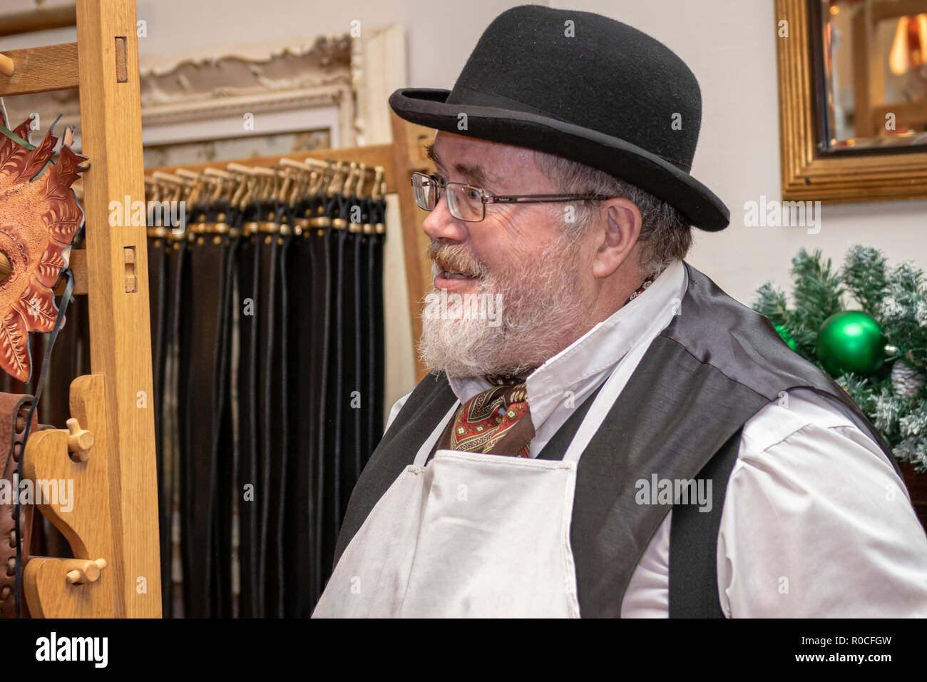 UK, Market Bosworth, Victorian Christmas Fair - December 2015: market trader selling leather goods dressed  as a victorian shopkeeper - Stock Image