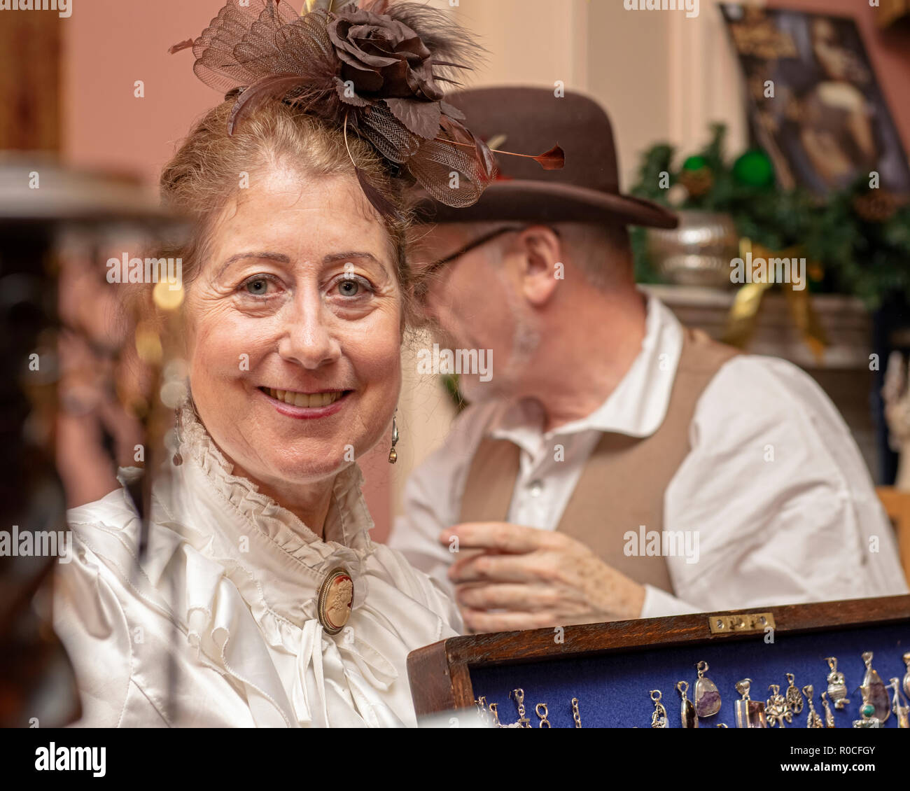 UK, Market Bosworth, Victorian Christmas Fair - December 2015: A couple of re-enactors sell jewelry at a market stall - Stock Image