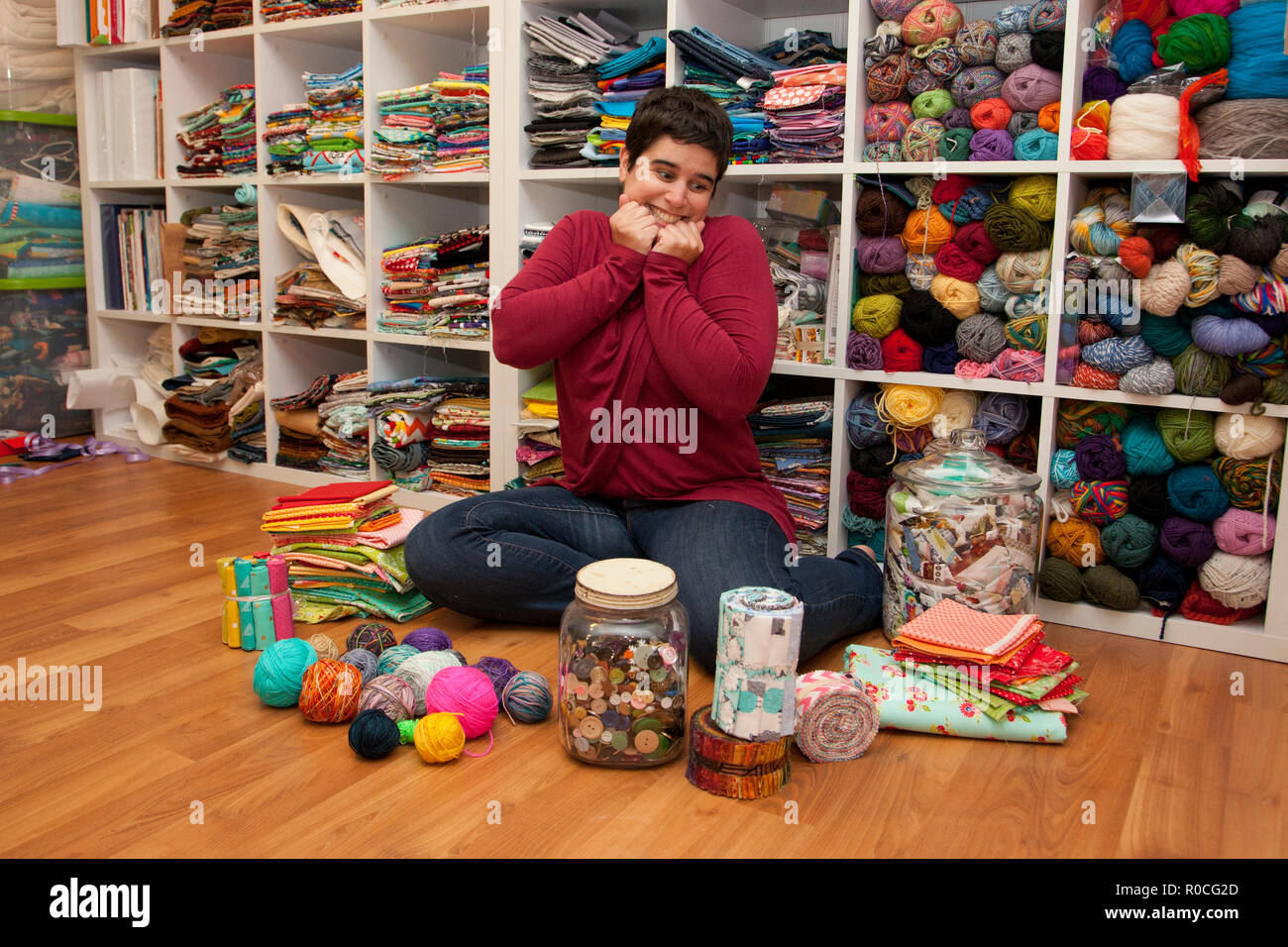 Person surrounded by fabric, yarn, looking gleeful and excited to create - Stock Image