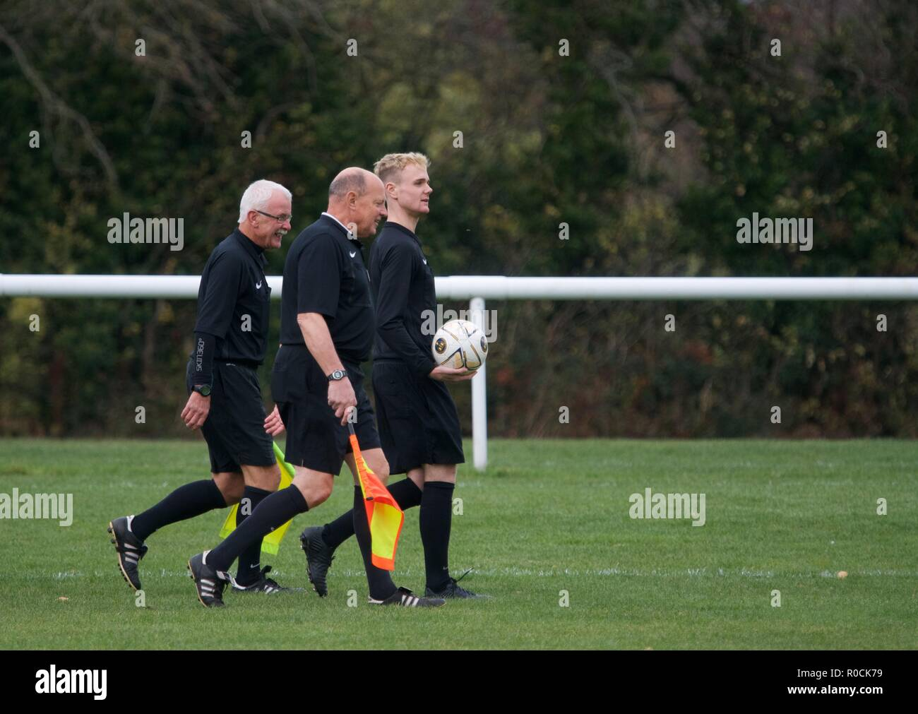 The referee and his assistants walk to the centre circle before  the start of an amateur football match between Whaley Bridge Athletic and Malpas. - Stock Image