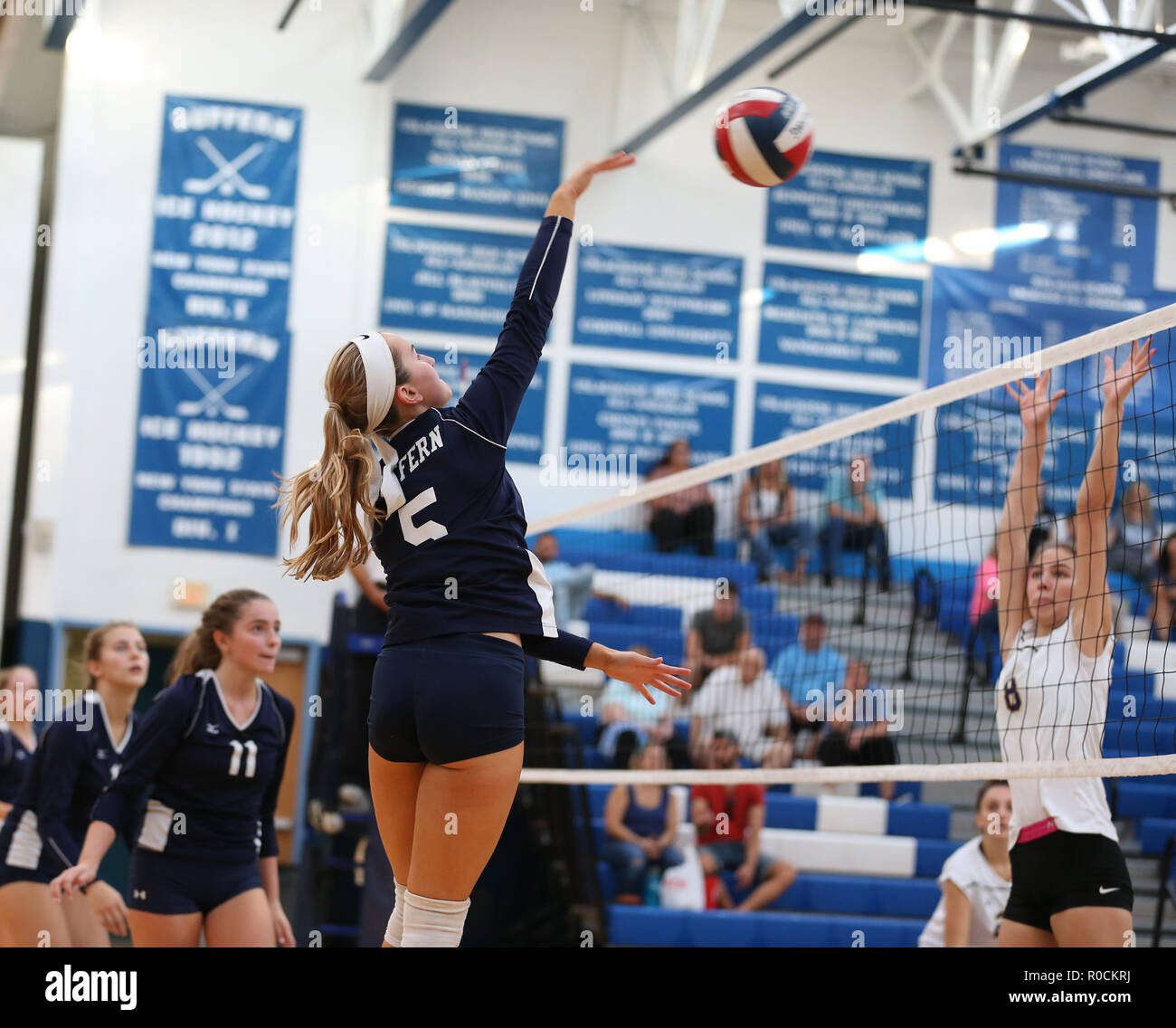 Girls high school volleyball game in a high school gym - Stock Image