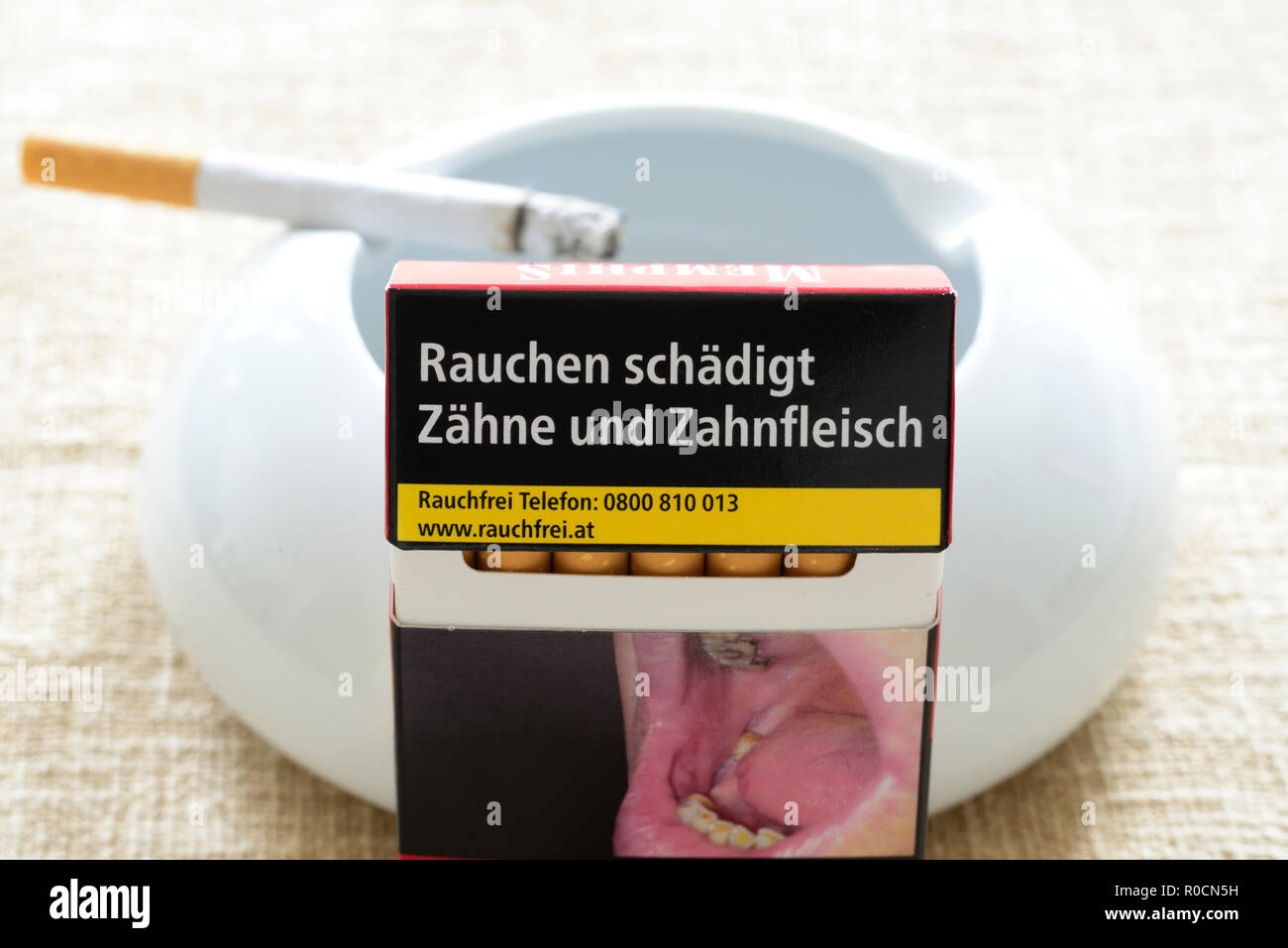Pack of cigarettes with the warning smoking harms teeth and gums. - Stock Image
