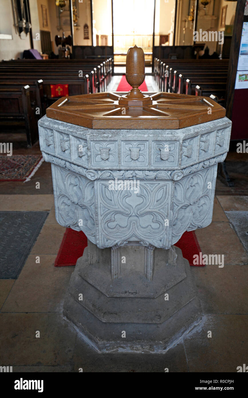 Carved stone Font at Sherborne St Mary Magdelene church. Gloucestershire, Cotswolds. - Stock Image