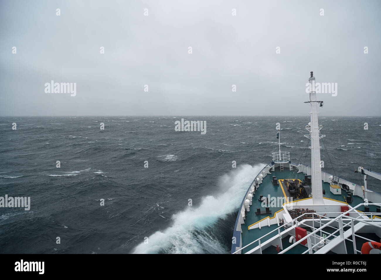 Ship cruising in storm and heavy seas crossing the Denmark Strait between Greenland and Iceland. Stock Photo