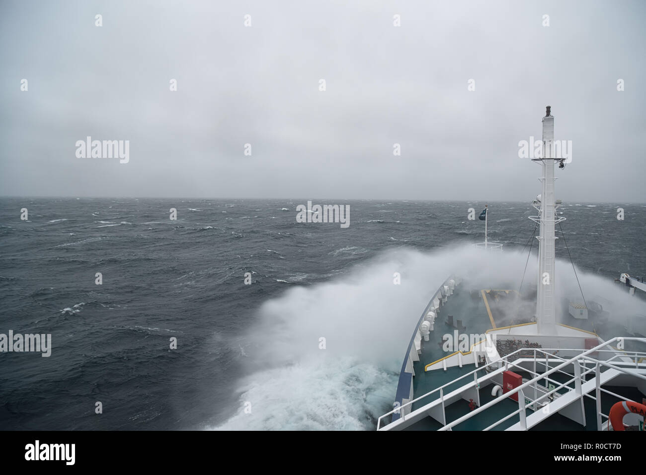 Ship cruising in storm and heavy seas crossing the Denmark Strait between Greenland and Iceland. - Stock Image