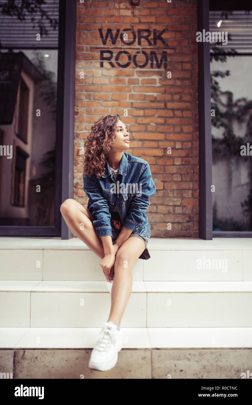 Young latin woman sitting on stairs in front of a brick wall. - Stock Image