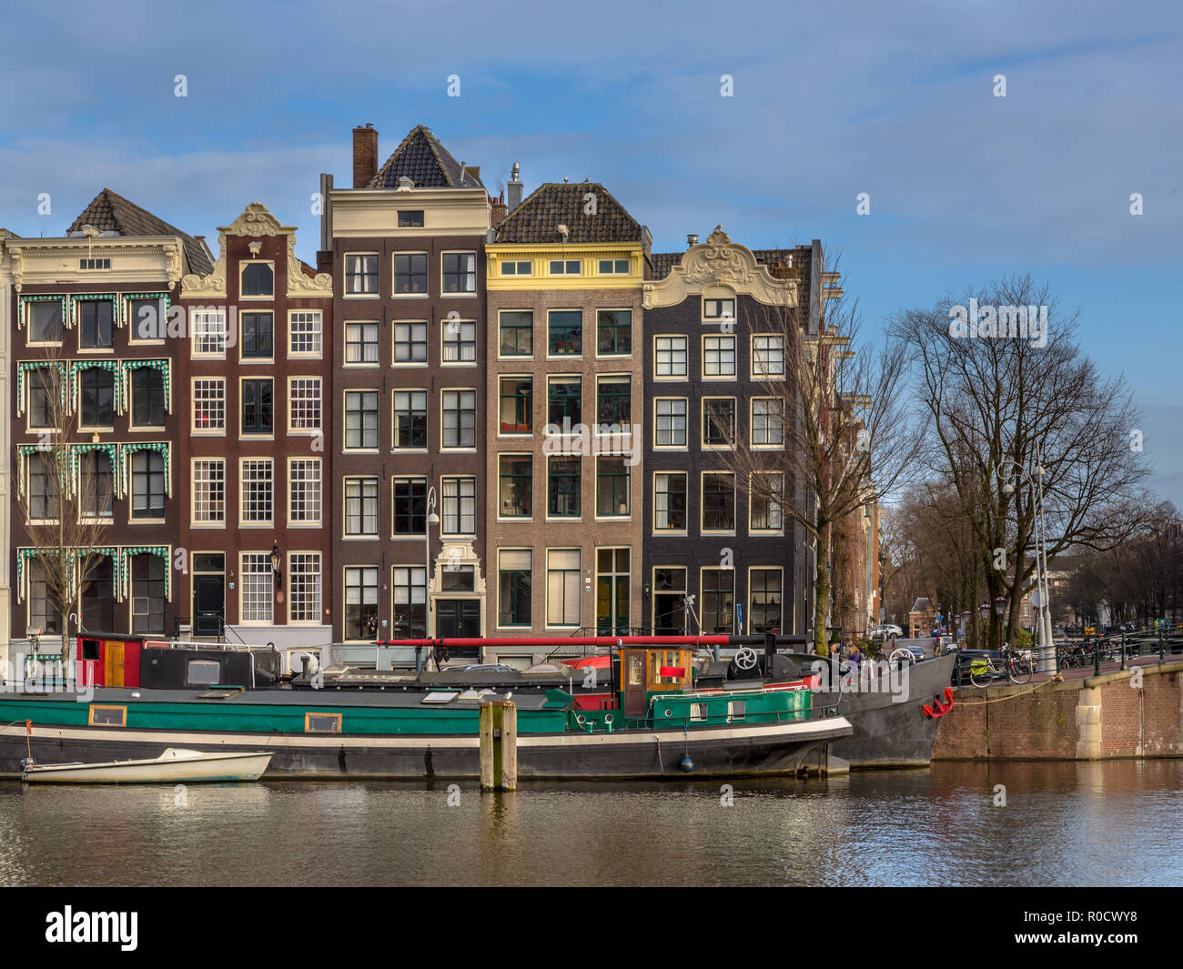 Colorful traditional canal houses and boats in the UNESCO World Heritage site of Amsterdam on the corner of Amstel and Nieuwe Prinsengracht - Stock Image