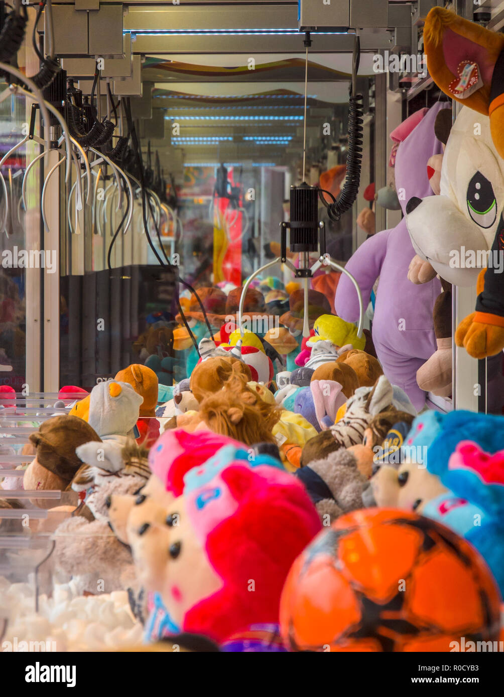 Claw crane with soft cuddly toys in an arcade machine - Stock Image