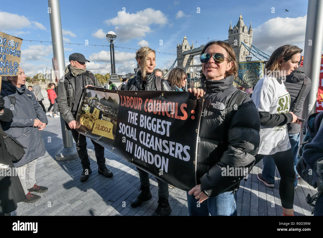 London, UK. 3rd November 2018. Several hundred people, mainly from London's council estates under threat of demolition by Labour London councils came to a protest outside City Hall called by 'Axe the Housing Act'. Class War brought a banner shaming Labour Councils as the Biggest Social Cleansers in London. The protest called for an end to estate demolitions unless  approved by a ballot of all residents, and for public land to be used to build more council homes rather than being turned over to developers to make huge profits from high-priced flats. Speaker after speaker from estate after estat - Stock Image