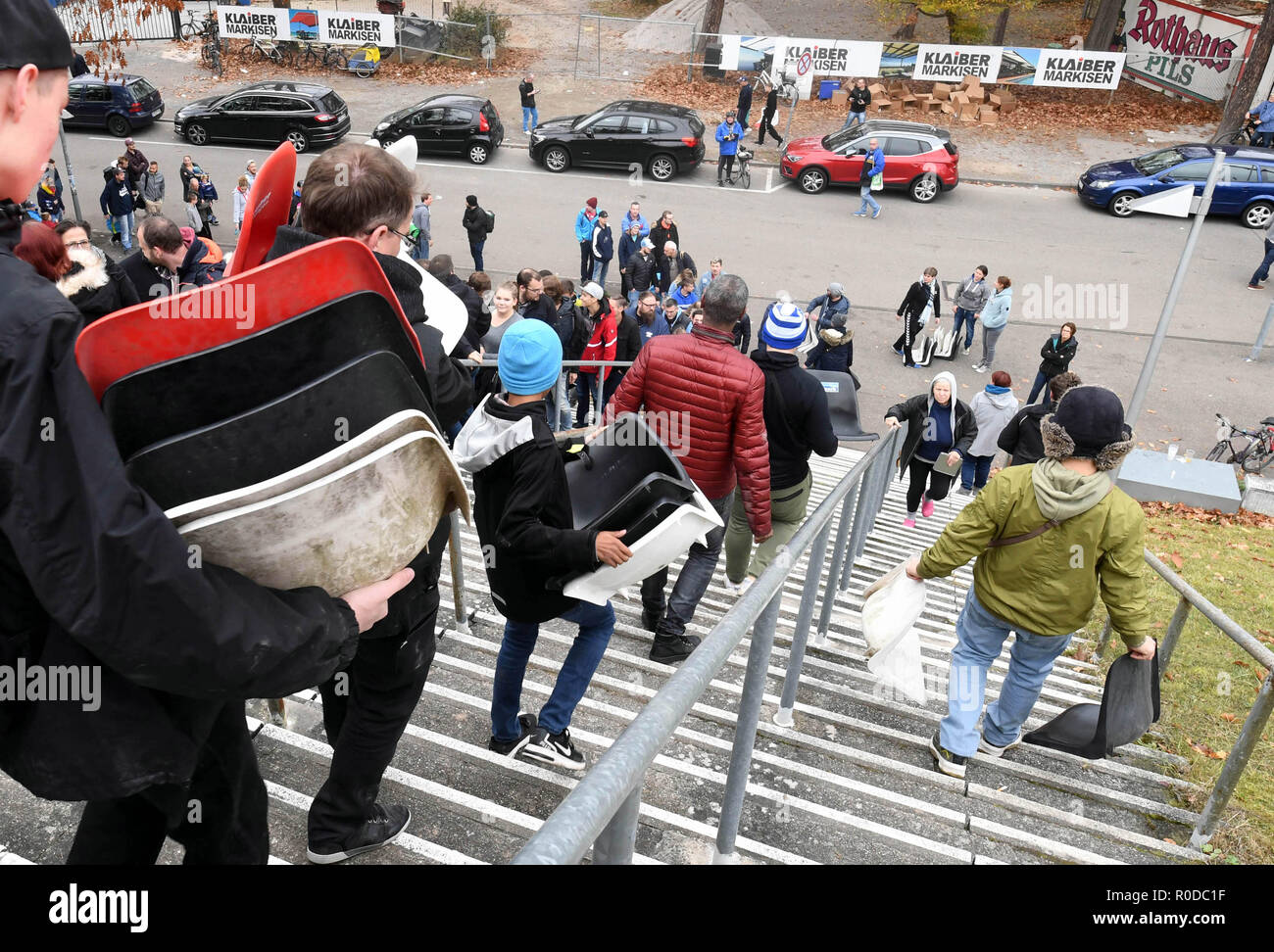 Karlsruhe, Germany. 04th Nov, 2018. Fans of the third-league soccer team Karlsruher SC wear seat shells from the Wildparkstadion Karlsruhe, which they previously dismantled there. Before the demolition work on blocks A1 to A4 begins in the stadium on 05.11.2018, KSC fans can secure up to ten seat shells for five euros each. According to the association, the proceeds from the fan campaign will be donated to the youngsters of Karlsruher SC. Credit: Uli Deck/dpa/Alamy Live News - Stock Image