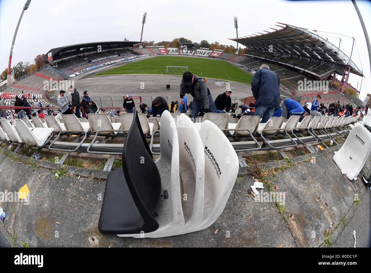 Karlsruhe, Germany. 04th Nov, 2018. Fans of the third-league soccer team Karlsruher SC dismantle seat shells in the Wildparkstadion Karlsruhe. Before the demolition work on blocks A1 to A4 begins in the stadium on 05.11.2018, KSC fans can secure up to ten seat shells for five euros each. According to the association, the proceeds from the fan campaign will be donated to the youngsters of Karlsruher SC. Credit: Uli Deck/dpa/Alamy Live News - Stock Image