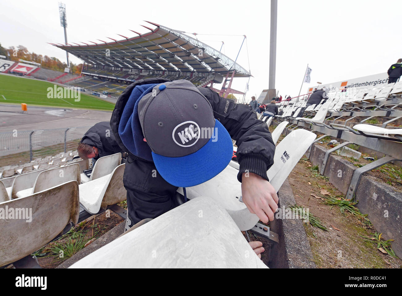 04 November 2018, Baden-Wuerttemberg, Karlsruhe: Fans of the third-league soccer team Karlsruher SC dismantle seat shells in the Wildparkstadion Karlsruhe. Before the demolition work on blocks A1 to A4 begins in the stadium on 05.11.2018, KSC fans can secure up to ten seat shells for five euros each. According to the association, the proceeds from the fan campaign will be donated to the youngsters of Karlsruher SC. Photo: Uli Deck/dpa - Stock Image