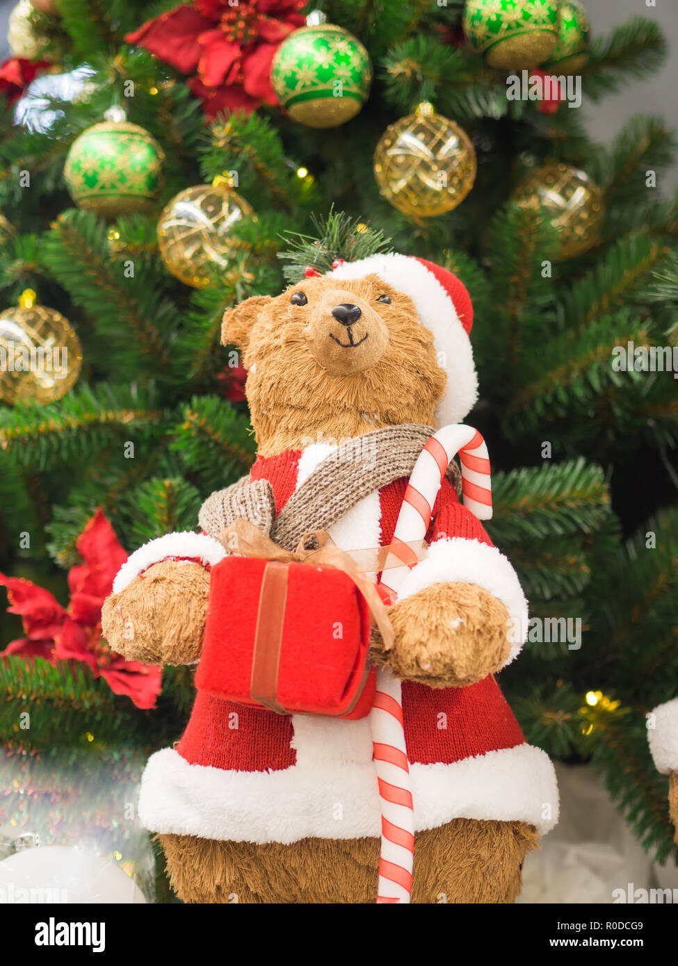 26ff679f41 A toy bear dressed as Santa Claus standing against a Christmas tree holding  a gift box. Christmas and New Year concept.