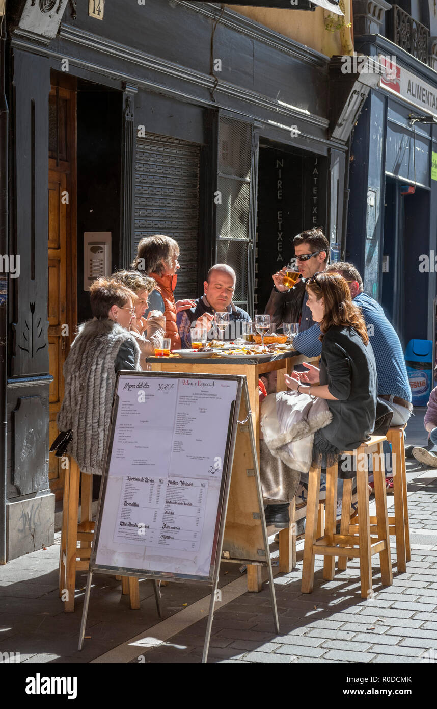 People sitting outside a bar in the old town (casco antiguo), Calle Mercaderes, Pamplona, Navarra, Spain - Stock Image