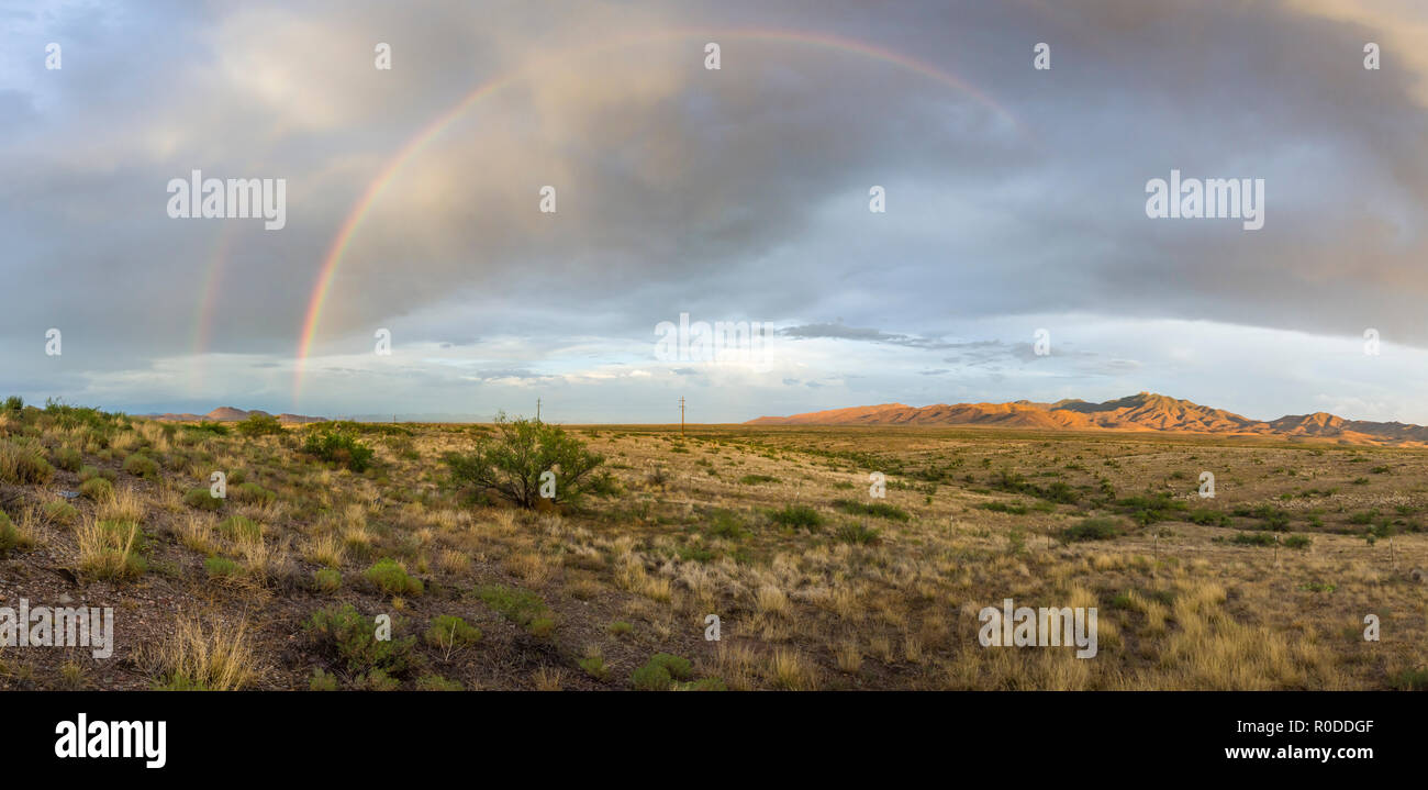 A double rainbow visible to the east as sun sets on the high desert of SE Arizona (panorama) - Stock Image