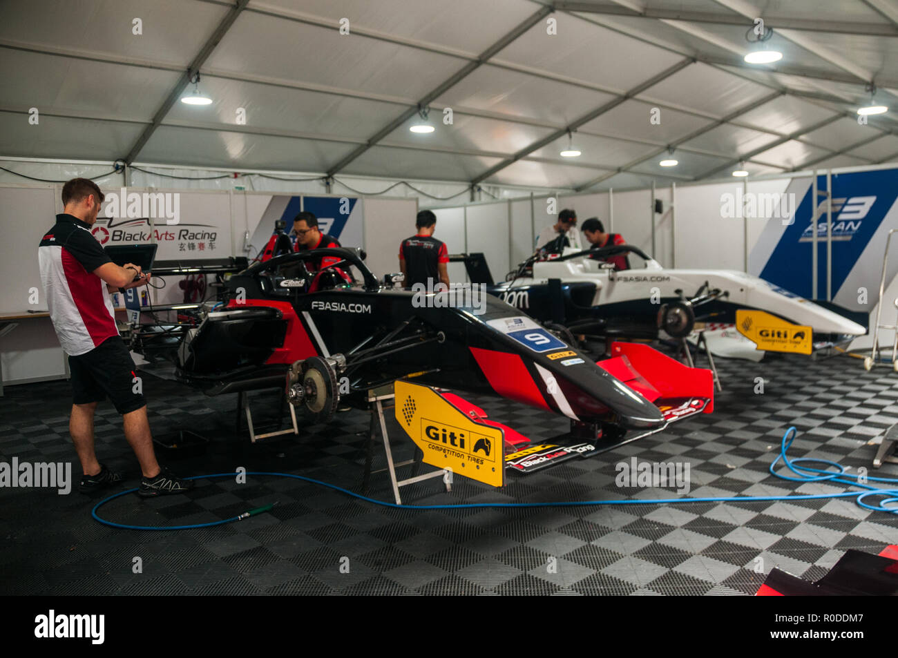 Black Arts Racing team F3 Asia racing cars undergoing maintenance in the pits of the Shanghai Circuit. - Stock Image