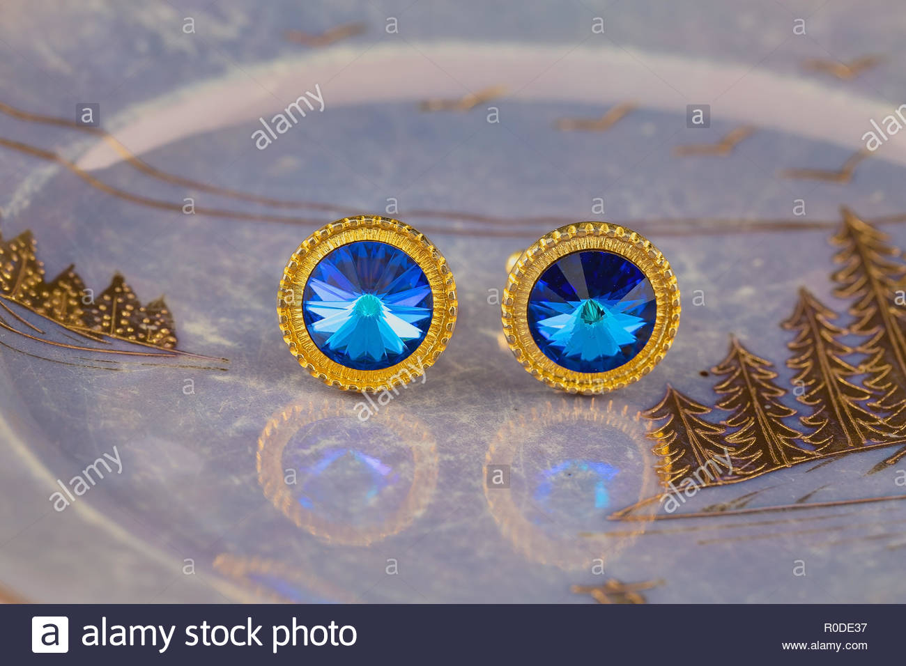 Vintage large gold blue stone cuff links on a lustrous plate - Stock Image