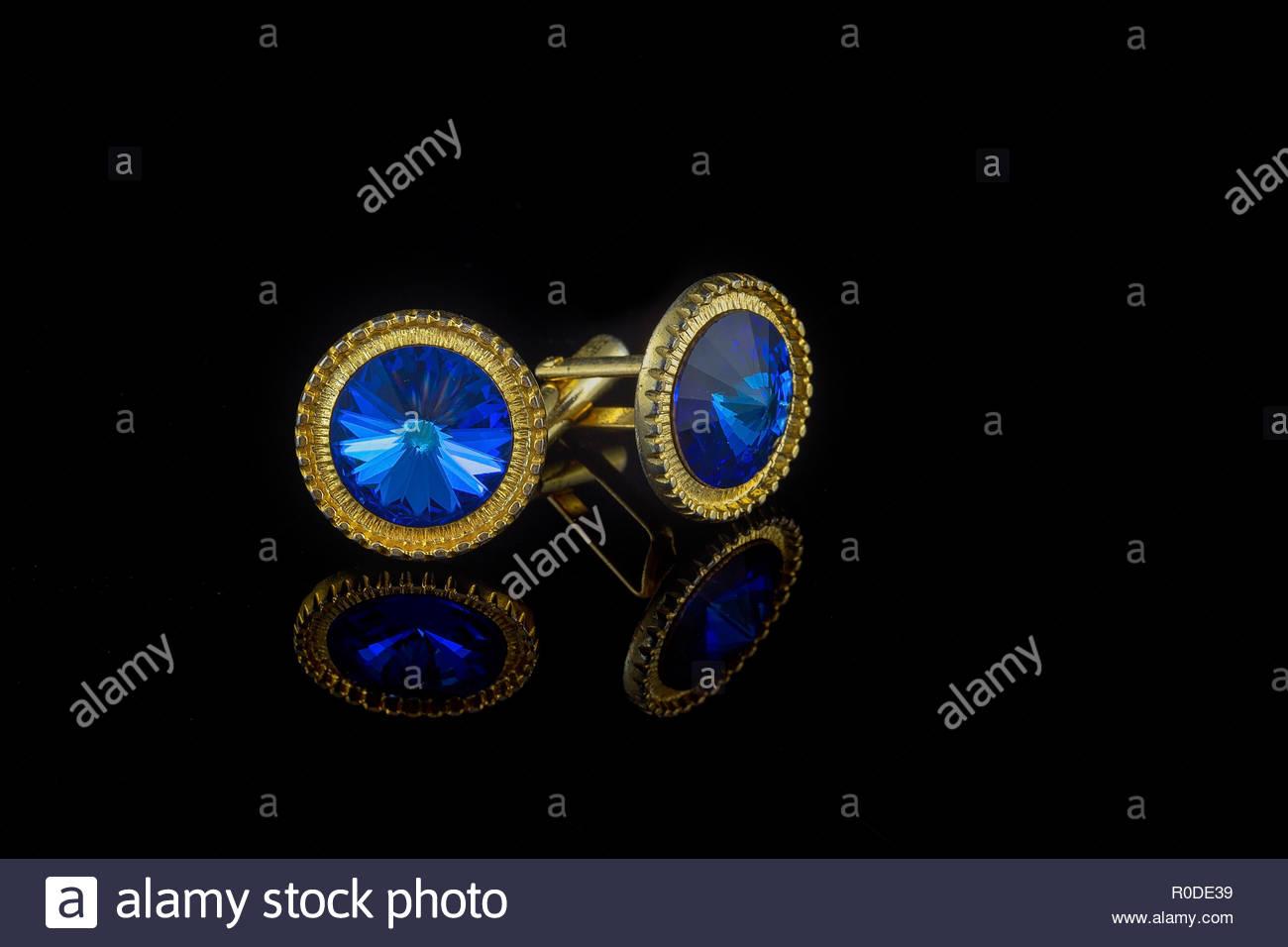 Vintage large gold blue stone cuff links on black background - Stock Image