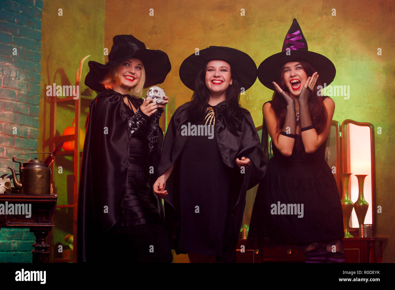 Picture of three witches in black hats in dark room against mirror and rack - Stock Image