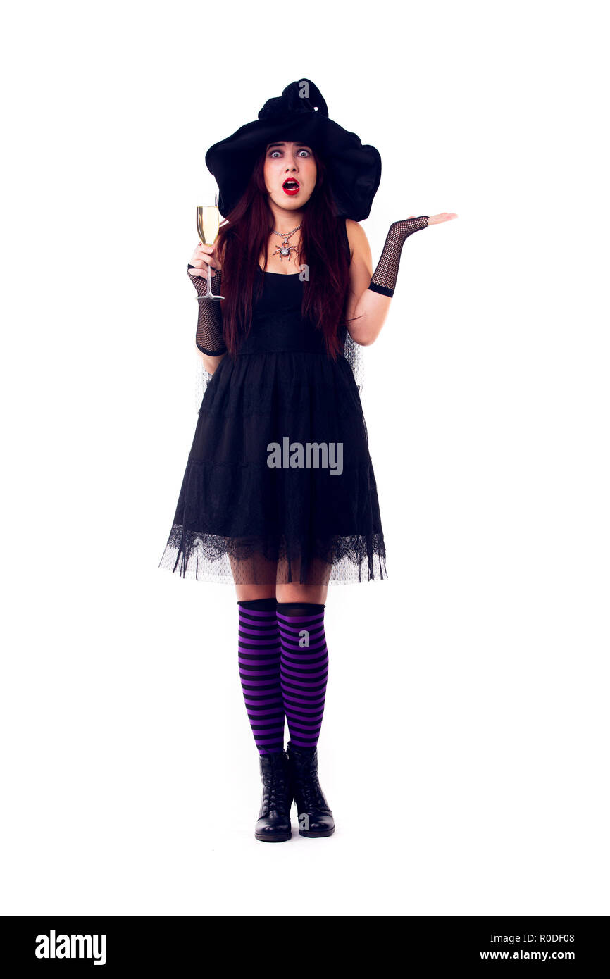 Full-length photo of surprised witch with wine glass with wine in black dress and hat - Stock Image